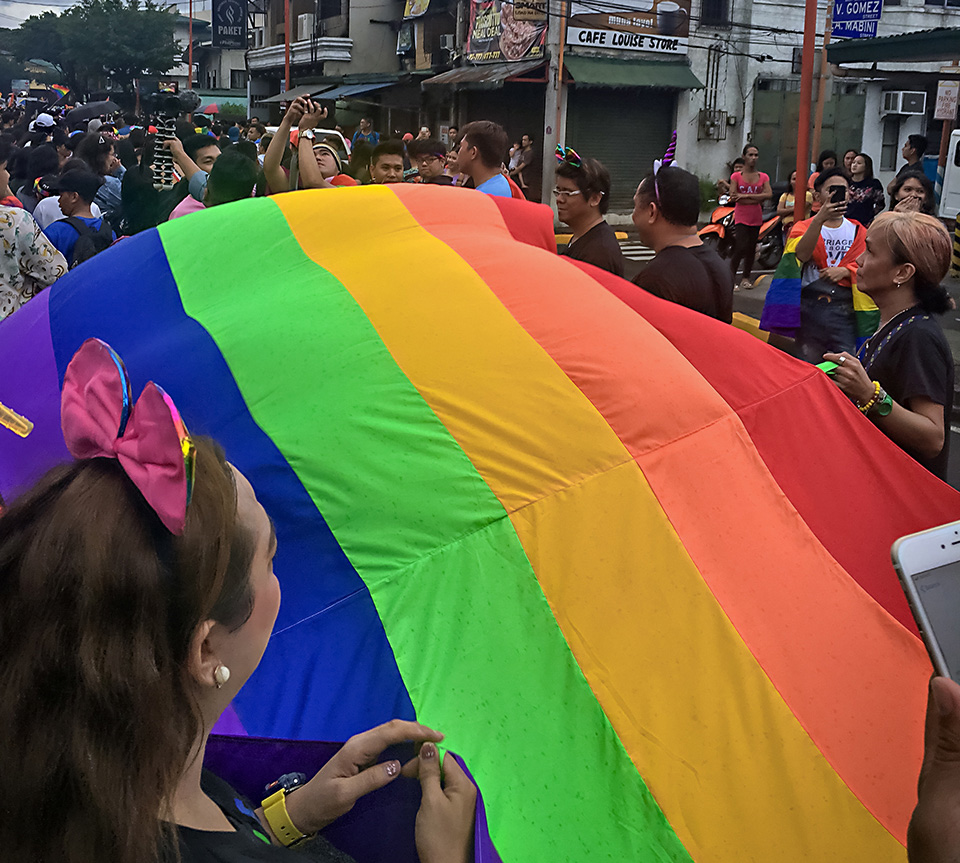 A group of marchers walk with a giant rainbow flag at the 29 June Pride march in Manila. Photo: UN Women/Rebecca Singleton
