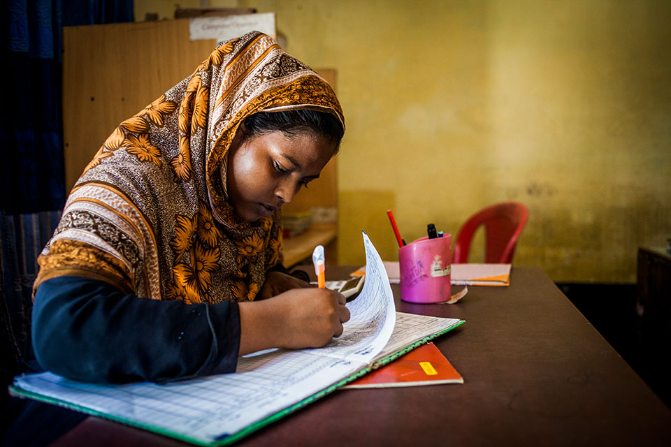 A worker checks in her daily attendance sheet at Ghop Nawapara Road in Jessore. Photo: UN Women/Fahad Kaizer