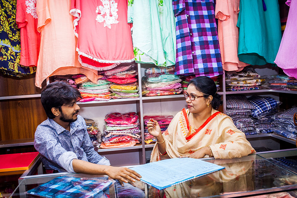 Parveen Akter, at right, owner of Glamour Fashion House, overseeing business with her elder son, Ridoy, at Jessore Bazar area. Photo: UN Women/Fahad Kaizer