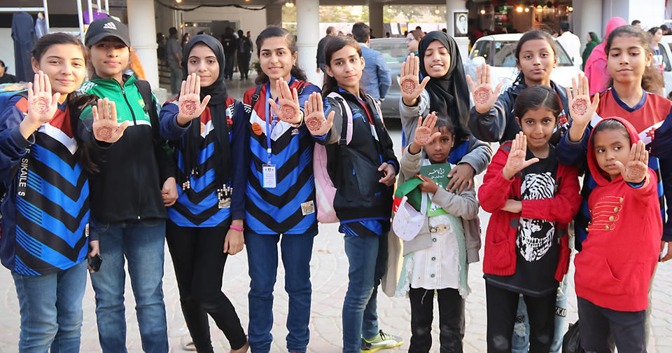 Young students from Karachi send out the message with their dyed palms: stop dowry mongering. Photo: UN Women/Habib Asgher