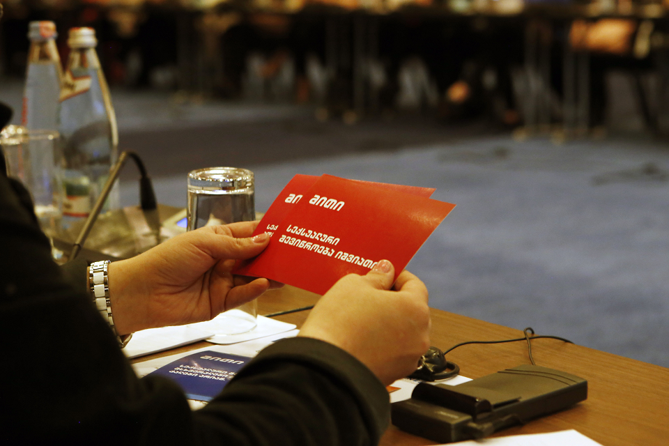 The woman is getting acquainted with the communications materials on sexual harassment. Photo: UN Women/Maka Gogaladze
