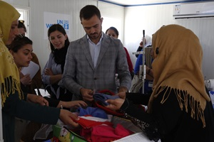 Visiting the tailoring facility, women present the baby kits that they manufacture. The production of the baby kits within the tailoring center are distributed through field hospitals to the more than 400 babies born in camp every month.