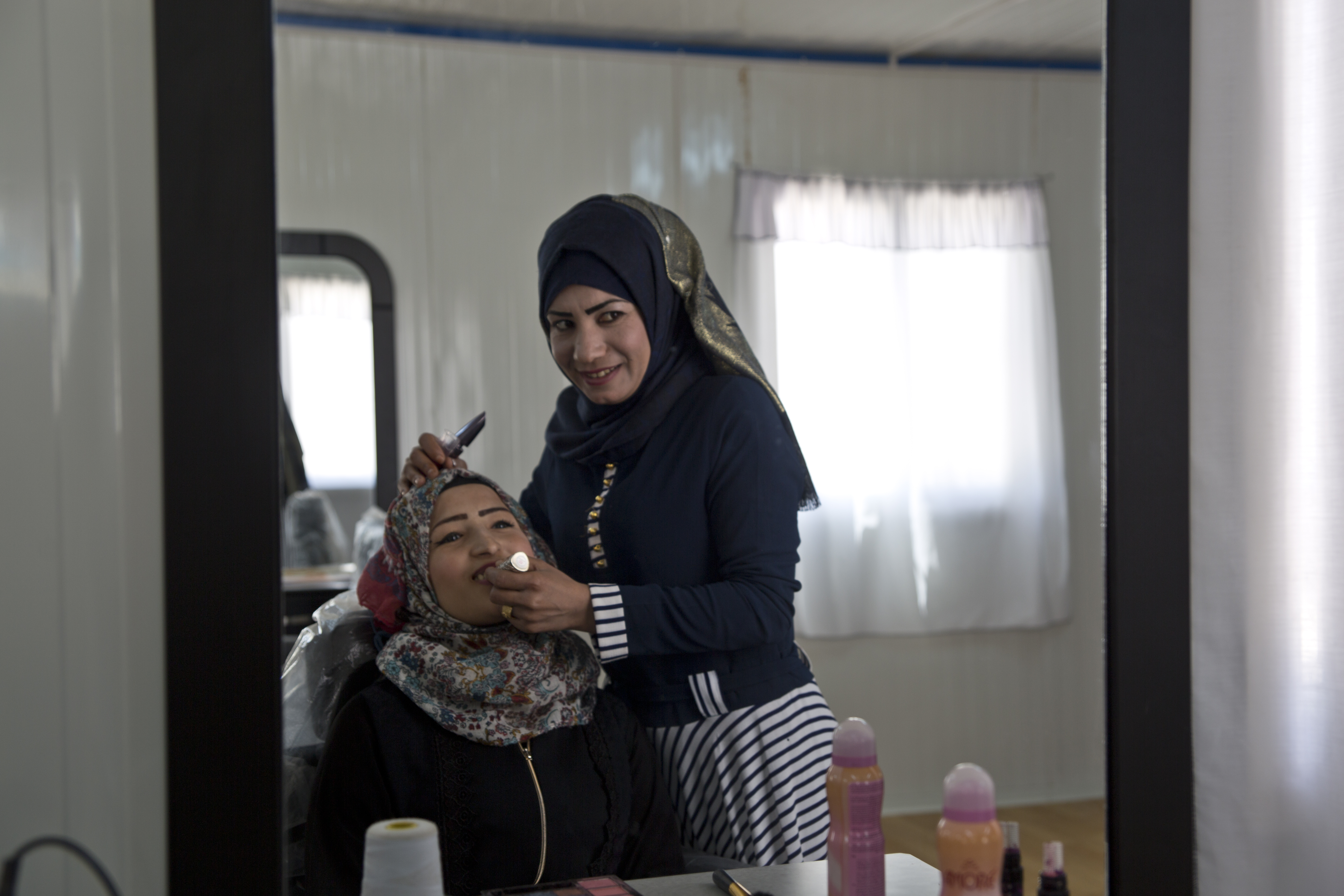 Intesar Hassan supports her family by working as a beautician within the cash-for-work program within the Azraq UN Women Oasis for 'Women and Girls.' Photo source: UN Women/Lauren Rooney