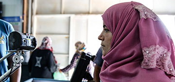 Before the lockdown went into effect, a UN Women beneficiary gets her iris scanned, allowing her to buy groceries at the Sameh Mall Supermarket in Azraq refugee camp, Jordan. Photo: UN Women/Lauren Rooney