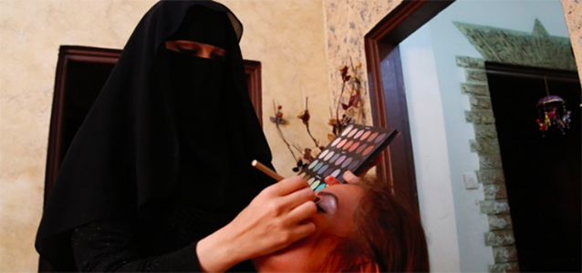 Manal Barham, 33, applies make-up on one of her clients in her home-based beauty salon in Hasmi Shamali, East Amman. Photo Credit: UN Women/ Lauren Rooney.