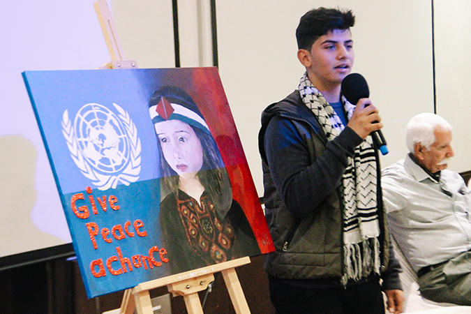Young Palestinian presents his drawing made for the Open Day