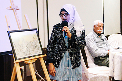 Palestinian student explains the meaning of her drawing made for the Open Day to the participants
