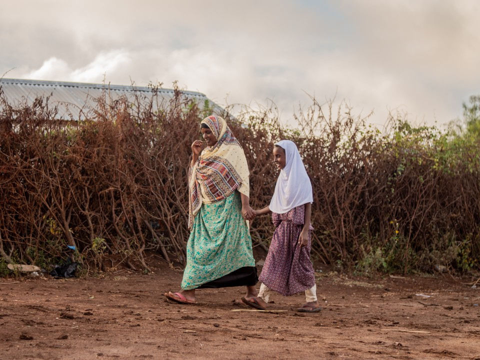 A woman and girl participating in a project from ISF walk together. Muhammed Isra, photographer: Nyasha Kadandara, place: Magalo cad