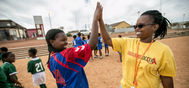 """SKILLZ Coach Sonwabise (Sony) Dick celebrates with Grassroot Soccer SKILLZ Street graduate and volunteer, 15-year-old Yamkela Nqweniso, after a successful afternoon of SKILLZ HIV-awareness activities with female SKILLZ participants in Khayelitsha, South Africa's fastest growing township."" Karin Schrembrucker/GRS"