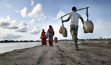 Rural villagers walk to and from a water well in Shatkhira, Bangladesh. 2010.