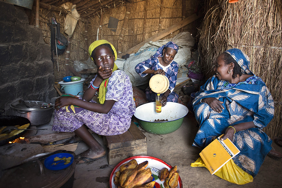 Nene (centre) and one of her daughters, Salamatou Abubakar (left), 12, have been providing food to many refugees at a makeshift restaurant in a small market at the camp. Photo: UN Women/Ryan Brown