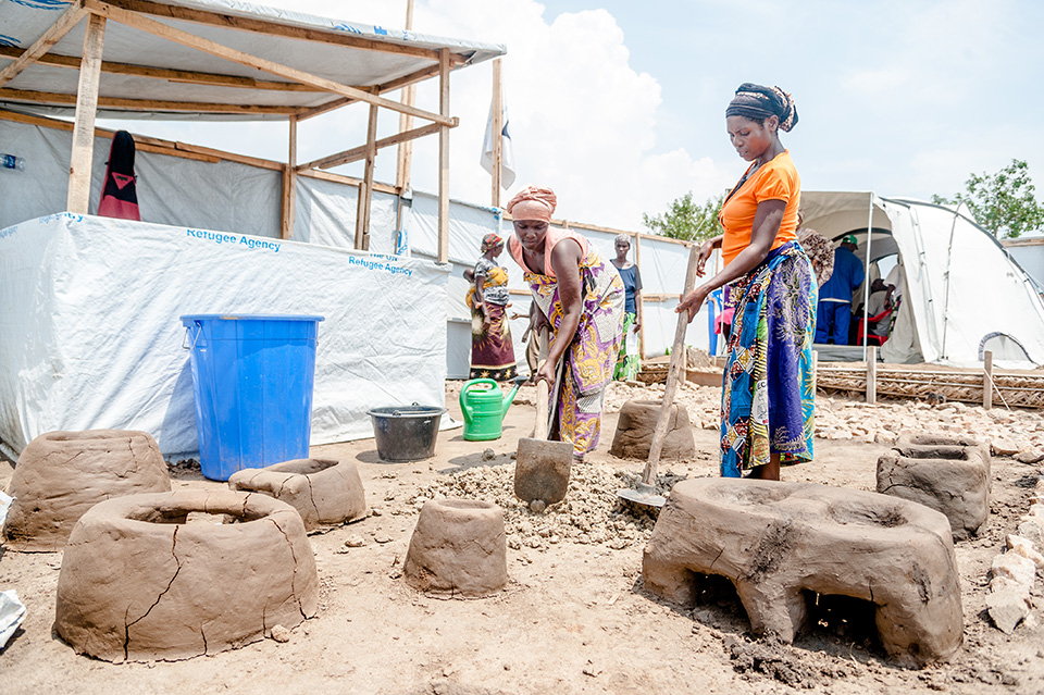 """Luscie, left, and Marita, right, work to make a handmade clay stove. At the multipurpose centres, they've learned to make stoves which help cut the cost of feeding their families. """"It takes less charcoal and the surface stays hot longer,"""" says Marita.  Photo: UN Women/Catianne Tijerina"""