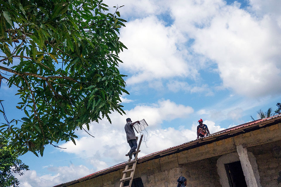 In Liberia, solar engineers install a solar panel on the roof of a village house, bringing electricity to this home for the first time. Photo: Thomas Dworzak/Magnum Photos for UN Women