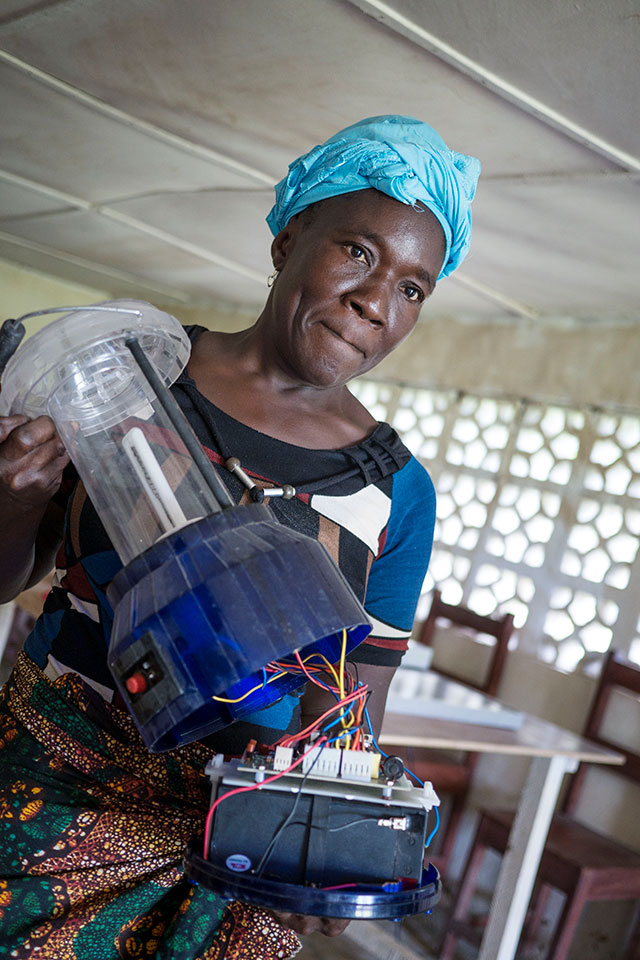 Bendu Sackie, a 55-year-old solar engineer displays the circuit board of a solar lantern that she assembled.