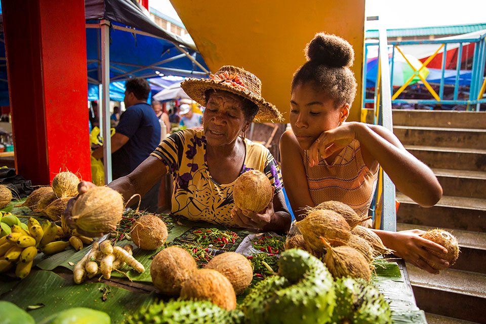 Mana Celestine (left) sells bananas, coconuts, papaya, chillis and soursop in the market in Victoria with the help of her granddaughter Anel. Photo: UN Women/Ryan Brown