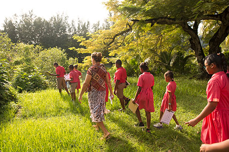 Christel Jacques, 55, leads her Wildlife Club of 8-year-old children on an outing to learn about mangroves. Photo: UN Women/Ryan Brown