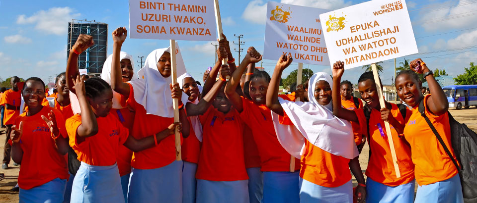 """Young school girls organize themselves before the March to End Gender-Based Violence in Dar es Salaam, Tanzania. One sign reads: """"Refrain from using abusive language for Women and Children""""  Photo: UN Women/Deepika Nath"""