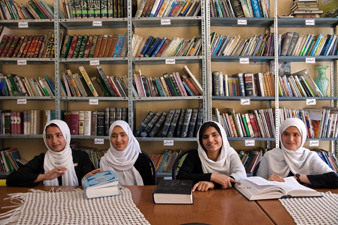 Four young women in front of bookcase in Afghanistan. Photo: World Bank/Graham Crouch