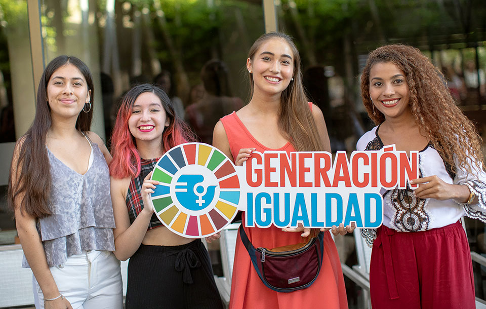 Young women in Mexico hold up Generation Equality signs.