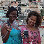 Girls display a mobile app against violence in a shantytown in Rio de Janeiro, Brazil