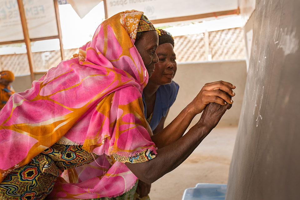 A woman in a refugee camp in Cameroon learns to write. Credit: UN Women/Ryan Brown