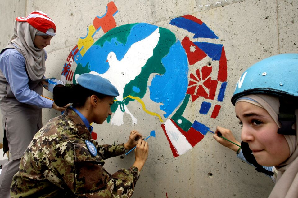 Three women paint a mural symbolizing peace on a wall.