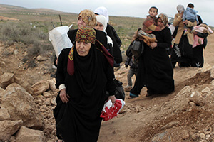 A line of Syrian refugee women, some carrying children, cross into Jordan from southern Syria in February 2013. Photo credit: UNHCR/N. Douad