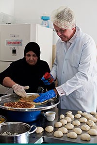 UN Women Deputy Executive Director John Hendra participates in a demonstration of the Women-Run School Canteen Project at the Anata Sabaya Centre.Photo: UN Women/Loulou d'Aki