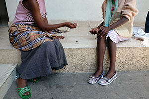 Two young girls play a game at the Safe House where they live in Adama. Photo: Felix Eldridge.