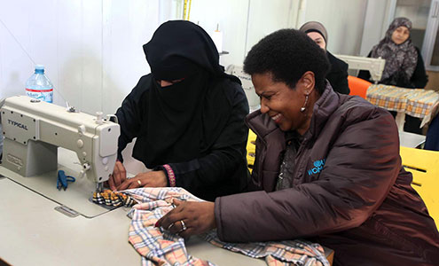 UN Women Executive Director Phumzile Mlambo-Ngcuka takes part in tailoring activities during a visit to the Za'atari refugee camp for Syrian refugees during her trip to Jordan from 20 to 23 February 2014. Photo: UN Women Jordan/Abdullah Ayoub