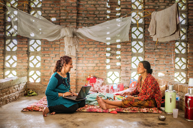 Sujata sharma Poudel, supervisor  of the Center for Victims of Torture and a psychosocial counsellor sits with a survivor  in Panchkhal on July 1,2015