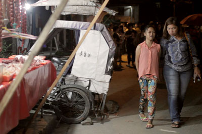 A city official is paired with a young girl to survey the night markets in Barangay Bagong Silangan as part of a Women's Safety Audit on 4 September, 2015. Photo: UN Women/Hubert Tibi