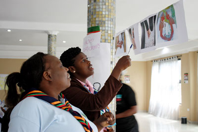 What constitutes a healthy or an unhealthy relationship? Participants examine photographs as part of a train-the-trainers workshop in Zambia. Photo: UN Women/Urjasi Rudra
