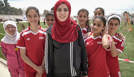 Syrian refugee and Jordanian girls participate in a mixed-nationality football camp in Jordan. Photo: UN Women/Christopher Herwig