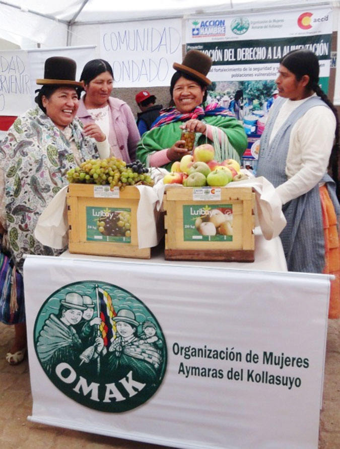 Lucrecia and classmates from the Organización de Mujeres Aymaras de Kollasuyo (OMAK) display products they grew in the community of Luribay without agrochemicals to support their economic empowerment. Photo: OMAK.