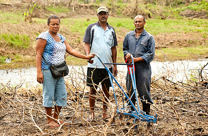 Lusiana Bulu (Secretary of the Ba Market Vendors Association) with Rakesh Prakash and his brother Sanesh Kumar on their farm just outside of Ba. Flooding destroyed much of the crops, leaving them with bare twigs and rotten eggplants. Photo: UN Women/Murray Lloyd