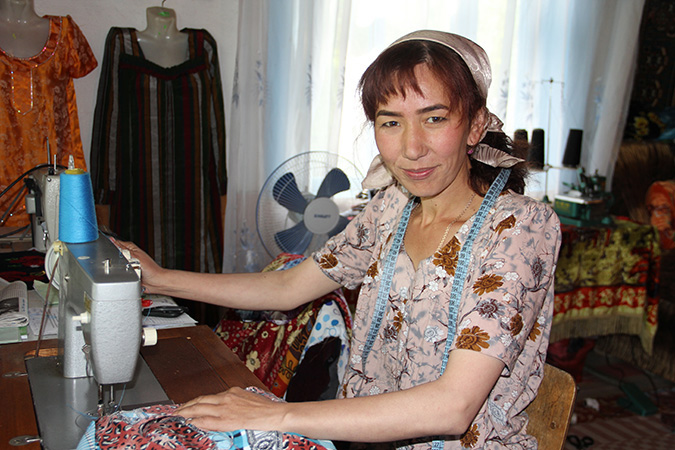 Sayokhat Tashbekova welcomes visitors into her workshop where she, along with other abandoned wives of Tajik migrant workers, creates traditional crafts for sale. Photo: UN Women