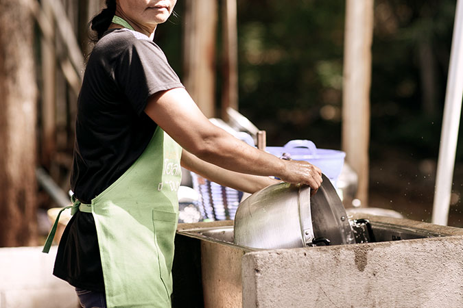 A woman migrant worker washes pots in Bangkok, Thailand. Photo: UN Women/Pornvit Visitoran