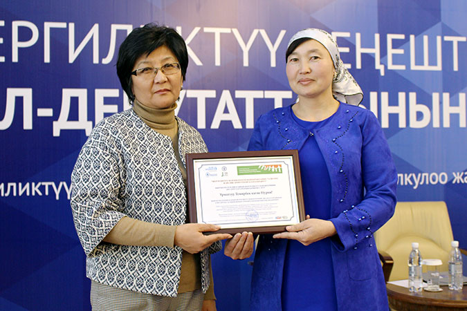 Taalaigul Isakunova, Minister of Labour and Social Development of the Kyrgyz Republic, is congratulates Nuriya Temirbek kyzy for being elected as a deputy of a local council. Photo: UN Women/Meriza Emilbekova
