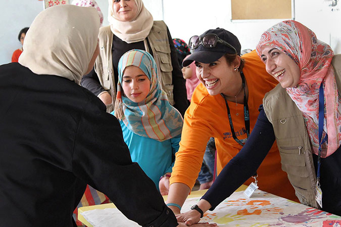 Hadeel Al-Zoubi, in orange, leading creative activities with Syrian refugee children to commemorate World Refugee Day in 2015 at the UN Women Oasis in the Za'tari refugee camp. Photo: UN Women/Christopher Herwig