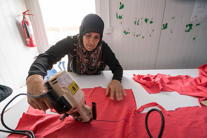 Women work as tailors producing baby clothes in the cash-for-work programme in the UN Women-run Oasis in the Za'atari refugee camp. Photo: UN Women/Christopher Herwig