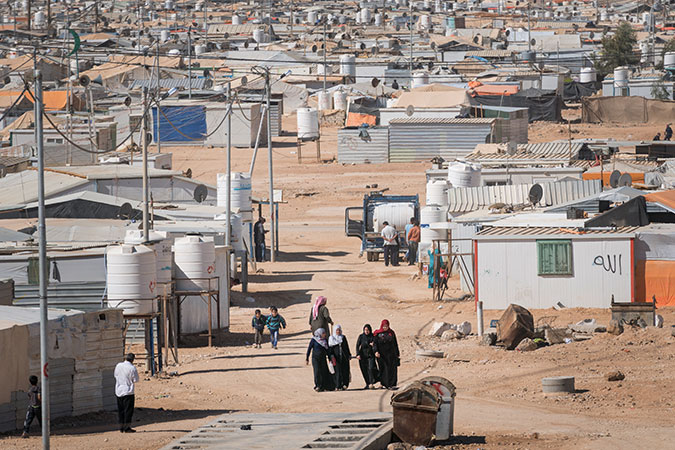 Women walk through the Za'atari camp. Photo: UN Women/Christopher Herwig