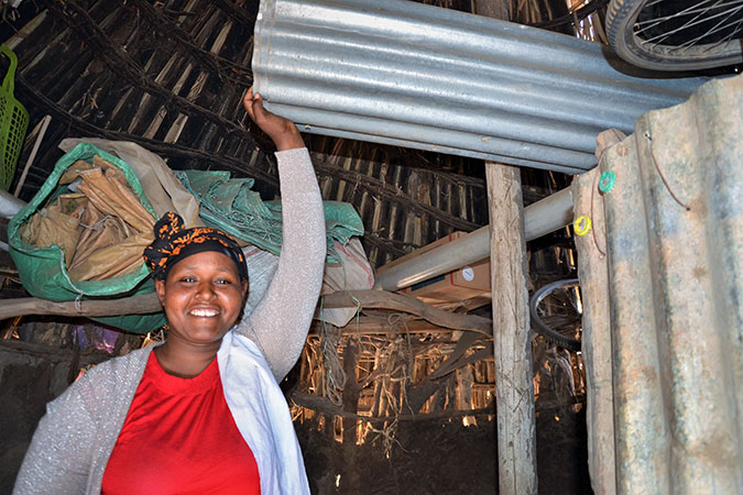 Kebela Guru shows the corrugated iron sheets she purchased to build a new home for herself. Photo: UN Women/Fikerte Abebe