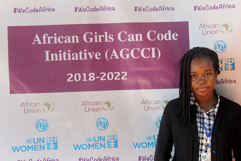 Eno Ekanem poses in front of a African Girls Can Code Initiative sign. Photo: UN Women/Faith Bwibo