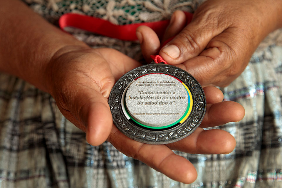 On 21 February, 2018, two years since the historic Sepur Zarco judgment, the Public Ministry of Guatemala, together with UN Women, presented a special medal of recognition to the 14 surviving grandmothers of the case.The Naxjolomi medallion, which in q'eqchi 'means, 'the one that leads', recognizes the leadership of the grandmothers who fought for justice and their continued leadership to ensure that the reparation measures become a reality. In this photo, Carmen Xol shows her medallion. Photo: UN Women/Ryan Brown