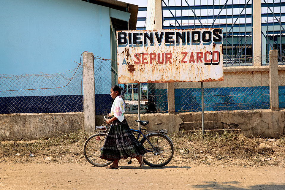 "A woman rolls her bike past a sign reading ""Bienvenidos Sepur Zarco"". Photo: UN Women/Ryan Brown"