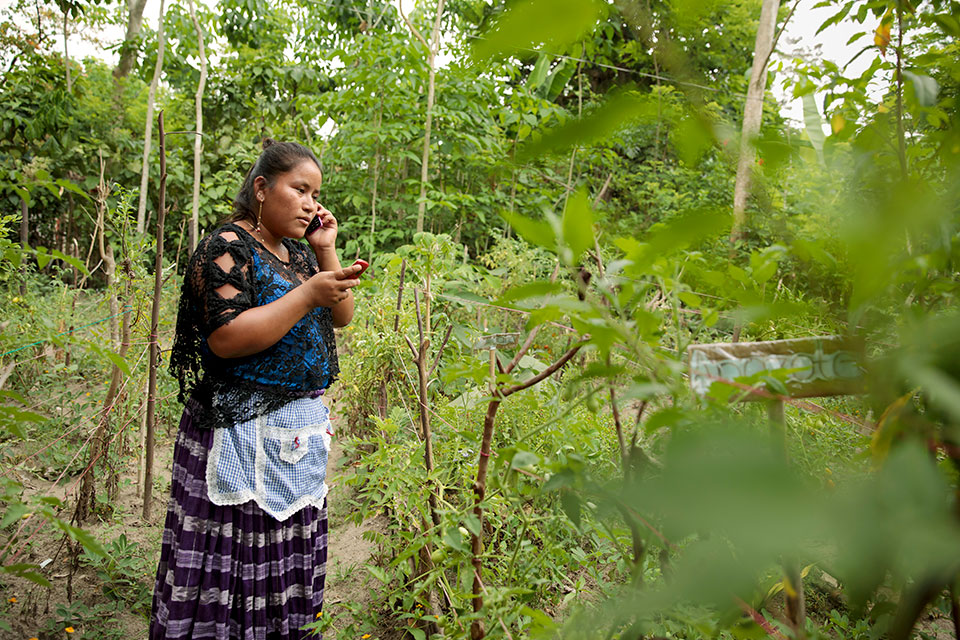 A woman speaks on her cell phone in a field in Guatemala. Photo: UN Women/Ryan Brown