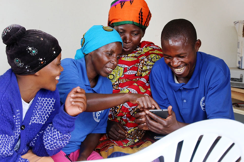 """Women and a man in Rwanda check the """"Buy From Women"""" mobile platform on a cell phone. Photo: UN Women/Sandra Hollinger"""