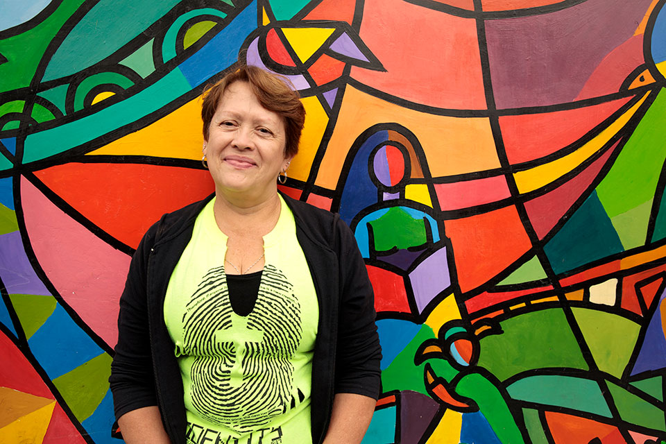 Alba Morena Fernandez, 56, resident of Zone 5, Guatemala City, poses in front of the mural residents painted as part of a larger initiative to engage women and their community in reclaiming streets, parks and public spaces, as part of the Safe City programme. Photo: UN Women/Ryan Brown