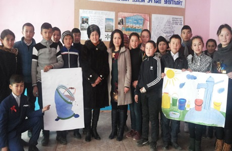 Erlan and his teammates with Ms. Roza Shamaeva, the head of the rural council. Photo: Un Women/Dildora Khamidova